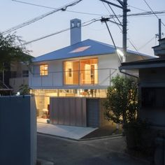 House in Kawanishi by Tato Architects  with hipped roof and stilts