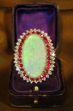 Giant 18K 16.55 Carat Opal Ring Crowned with 2.10 Carats of Fine VS Diamonds and 2.25 Carats of Red Rubies.