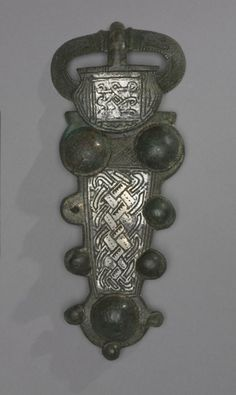 Buckle   Cleveland Museum of Art  Fibula, Buckle, 600s  Frankish, Migration period, 7th century  bronze and silver overlay, Overall - h:18.60 cm (h:7 5/16 inches). Andrew R. and Martha Holden Jennings Fund 1975.107