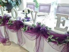 Purple organza table swagging, draped with faux ivy