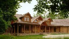 log homes with wrap around covered porches | The entry side offers a wrap around covered porch supported by flare ...