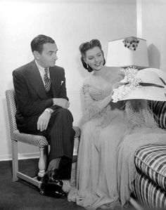 Irving Berlin seated in dressing room with Ann Miller, looking at hat on the set of Easter Parade (1948)