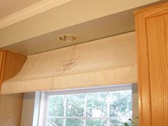 If you want to make your kitchen look like a French café, you can create an adorable awning with two tension rods and a fabric drop cloth. Sew a loop in the top of your drop cloth and slide the first tension rod in. Secure this rod directly under your ceiling. Place the second rod underneath the first one and a few inches away from the window to create the gentle slope of the awning.