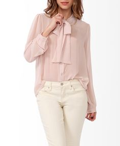 This sheer button up blouse featuring a round neckline with a self-tie collar. Full button placket. Long button cuffed sleeves. Finished hemline. Unlined. Woven. Lightweight