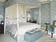 Upholstering the walls and bed canopy in the same damask fabric creates a cosseting effect in the master bedroom.