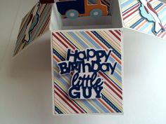 This handmade card is perfect for that special little guys birthday. As the recipient removes the flat card from the envelope they will be delighted as the card transforms into a whimsical box revealing a Happy Birthday Little Guy greeting, balloons, cars, planes, and gifts. The