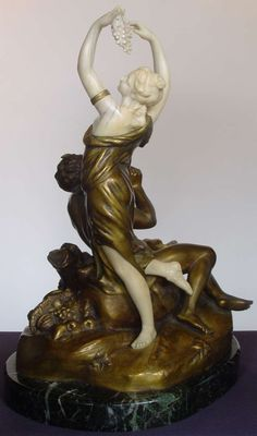 Dominique Alonzo (attributed)( French early 20th Century ) Student of Falguire and a frequent exhibitor at the Paris Salon. A large and rare bronze and ivory group depicting Pan and a Muse. Pan sit slasciviously gazing at a female Bacchanalian figure holding a bunch of grapes dancing in front of him, the base strewn with fruit and a basket.  Foundry registration number typical of Alonzo sculptures. Gold patination.  Dimensions: Total height 14 & 1/2 inches by 12 inches in width by 8 inches…