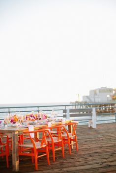 Pop-Up Santa Monica Pier weddings by Handmade Events with bright chairs at wooden table. -repinned from Los Angeles County, California marriage officiant https://OfficiantGuy.com #la #weddings