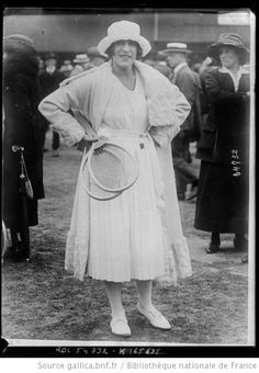 Suzanne Lenglen after winning Wimbledon in 1919. She is wearing a knockout outfit that features a knitted belt with pompoms and a coat trimmed with astrakhan.