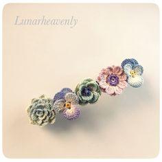 レース編みのお花を集めて、バレッタに仕立てました。パンジー、アネモネ、ダリア。深い青系のお花たちが髪を彩ります。こちらは生成りの糸で編んでいますので、アンティーク風の落ち着いた色合いになっております。<サイズ> 約縦1.8cm×横7cm(金具サイズは幅5mmで、小さめとなっております) <素材> 金具…真鍮 モチーフ…コットン ※型崩れしないよう加工してあります 通常レース編みで使われる20番・40番より細い、80番のレース糸で、モチーフひとつひとつ丁寧に編んでいます。パターンはすべてオリジナルです。故意に引っ張ることは型崩れや破損の原因となりますので避けてください。引っかけや擦れにもご注意下さい。お花のパーツはひとつひとつ染色してあります。水に濡れると色落ちや色移りの可能性があります。十分ご注意ください。