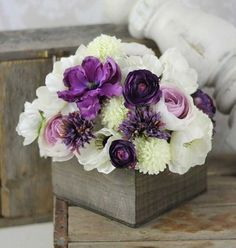 Faux Purple Floral Centerpiece: This unique bundle of faux flowers is perfectly situated in a charming wooden box. The contrast between the white and ivory base flowers and the deep violet hues of the accent flowers would complement a purple wedding theme. Of course, any color flower can be substituted in this centerpiece to tie in colors.