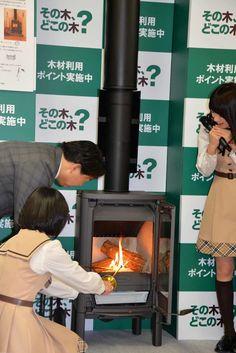 薪ストーブに火を入れる林芳正農林水産大臣と生駒里奈。