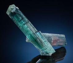 INDICOLITE Sapo Mine, Ferruginha, Conselheiro Pena, Doce Valley, Minas Gerais, Brazil  Here two doubly-terminated Indicolite prisms show aqua blue green of a gemmy transparent nature