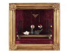 """Autómato musical, trabalho atribuível a Gustave Vichy (1839-1904). Interior da caixa representando teatro, com dois níveis de alturas e lados espelhados. No nível superior encontra-se uma malabarista deitada, segurando uma bola de riscas nas mãos e outra nos pés. Veste fato de seda, em mau estado de conservação. Cara em porcelana e olhos em vidro. Teatro forrado a veludo em tons de """"bordeaux"""" com aplicações a dourado. Moldura em madeira entalhada e dourada. Máquina em bom estado de…"""
