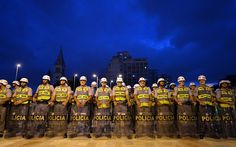 Police officers stand guard as demonstrators march against the upcoming FIFA World Cup Brazil 2014 and to demand better public transport services in Sao Paulo, Brazil