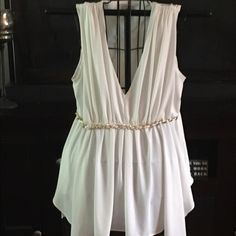 """Stunning Grecian-style blouse in tunic length. Gorgeous Grecian style sleeveless blouse.  Tunic length with a gathered, uneven hem.  Gold colored chain adorns front of waist.  Fully lined and not see-thru.  Stretchy and roomy.  Super flattering.  Approximately 27"""" from shoulder to longest point of hem. 95% rayon, 5% spandex. Cache Tops Blouses"""