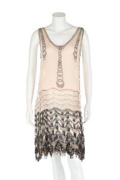 A couture beaded pale pink chiffon 'flapper' dress, circa 1928. A couture beaded pale pink chiffon 'flapper' dress, circa 1928. un-labelled, beaded with graduated chains to the bodice front and sides, the skirt with black and white undulating graduated beaded fringed bands, bust 86cm, 34in. - See more at: http://kerrytaylorauctions.com/one-item/?id=77&sub=%20&auctionid=429#.dpuf