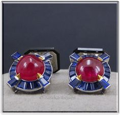 An Opulent Pair of Mens Art Deco Cufflinks in 18K White Gold, Two Oval Cabochon Cut Rubies(t.w. approx. 7.60 ct.'s), Surrounded by Thirty-Five Tapered Baguette Cut Natural Blue Sapphires(t.w. approx.1.8ct.'s), Just a Hit of Yellow Gold on the points of Setting Holding the Rubies, There are also  Brilliant Cut Diamonds and Onyx on the Reverse Side, ca.1925. These are absolutely phenominal!
