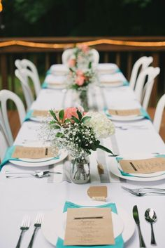 Anniversary party decor: Long tables with a striped runner and turquoise napkins.
