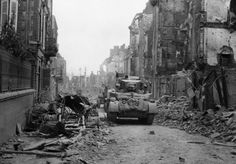 A British tank makes its way along a street in St. Lo with the battle still in progress, as the city is still fringed with Nazi guns which continually lob shells into the street in St. Lo, Normandy, France on June 20, 1944. Occasionally a brave soul walks down the street but his pace quickens as the shells explode.