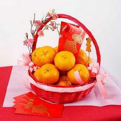 Chinese New Year display with mandarin oranges and red envelopes. I could use candace's old easter basket but I would use gold ribbon, not pink