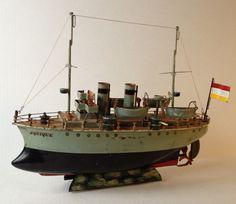 Croiseur Märklin, propulsion par mouvement d'horlogerie, armé de 4 canons, à tourelle mobile, 2 mats, 4 embarcations démontables, 2 cheminées, manches d'aération, passerelle, cabestan avec ancre, gouvernail réglable, pavillons avec matelots, officiers.