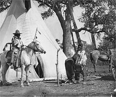 "Early 1900's Medicine Crow on horse with another man next to tipi in Montana. Tipi poles leaning against tree.  Hand written on edge of slide, ""Medicine Crow (standing), & friend at tipi."""