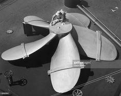 A man painting a huge ship's propeller, circa 1950.