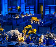Yellow Calla lilies and white hydrangeas, mixed with yellow-hued votive candles, brighten up a room awash in a rich navy hue.