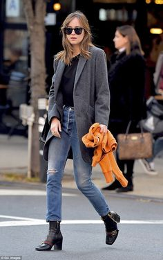 Simply sophisticated! Dakota Johnson wore a sophisticated grey coat, a pair of Gucci ankle boots, and blue ripped jeans during an outing in New York on wensday