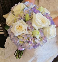 Fresh bouquet with ivory roses and purple hydrangea