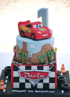 For Devins 1st birthday. 7 square, 6 round and 5 Lightning McQueen carved from rice crispy treats. I used my Cricut Cake to cut out Devins name Everything else is modeled from fondant.  I covered the board with glittery scrapbook paper and thought it looked just like asphalt/tarmac!  Turns out this cake was due a day earlier than I thought! Luckily, I was only 10 minutes from finishing when I got the call asking where I was!