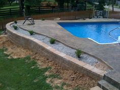 inground pool with retaining wall | An inground liner pool with a stamped concrete pool deck.