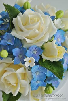 Cake topper made out of sugar flowers, sugar roses, sugar hydrangeas, buds and leaves