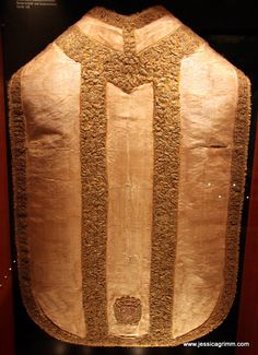 chasuble from the first half of the 17th century. It consists of a silk silver moire with bands of heavy gold and silk (yellow) embroidery. The gold embroidery consists of many small floral motives. It probably sparkled lovely in the candle light, but up close it looks a little too much and chaotic. On the lower back, the heraldic shield of the counts of Lodron, an Italian noble family is displayed.