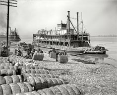 Mississippi riverboat loading bales of cotton.
