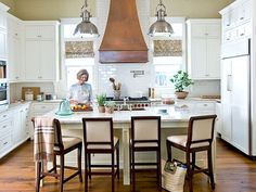 Ample brown barstools encourage kitchen visitors to linger. A copper vent hood makes the room appear taller by drawing the eye upward. A matching copper farmhouse sink is contrasted with a polished-nickel faucet and cabinet hardware. (Photo: Colleen Duffley)