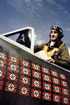 World War II in colour - England, circa 1945 Ace American pilot Lieutenant Colonel Francis S. Gabreski poses in a cockpit. The flags refer to the 28 enemy planes brought down by Gabreski. If you look closely above the swastikas it names the type of plane shot down.: