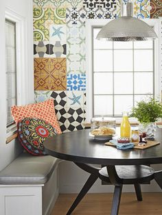 Nothing can compete with those tiles, so the rest of the breakfast nook is neutral: a dark stained table from West Elm, a white banquette with silver vinyl seat cushions (try fabric.com for a similar fabric), and a hammered metal pendant.