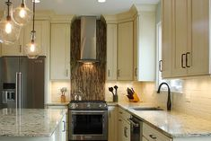 This light and bright kitchen features a stainless steel oven with a matching range hood. A brown and tan mosaic tile backsplash provides a stylish accent, while neutral wood cabinets and a subway tile backsplash are featured throughout the rest of the kitchen. Granite countertops finish off the look of the space.