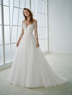Marvelous wedding dress with 3/4 sleeves, a ballgown skirt and an illusion bodice. A design with a two-piece effect that combines a voluminous tulle skirt with a crystal tulle bodice. It features thread embroidery and Chantilly appliqués that blend in with the skin.