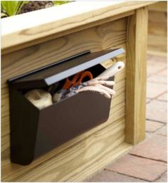 A mailbox attached to the side of a raised bed keeps pruners, gloves, twine and trowel within easy reach.