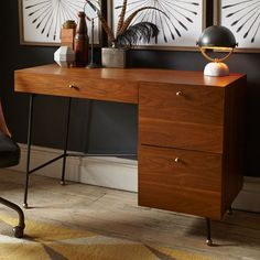 Lofted on slanted metal legs with antique brass-finished ball feet and hardware, the Grasshopper Desk is inspired by 1950s and '60s silhouettes. In a rich walnut finish, it provides three generous drawers.