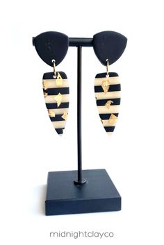 Black and translucent striped polymer clay earrings with gold leafing flecks. Edgy dagger shaped dangle earrings. Fun and trendy statement earrings make the perfect accessory for a summer date night outfit. Give as a unique birthday gift for girlfriend, hairdresser, or best friend. Makes a great graduation gift! Shop these trendy handmade earrings for women in my etsy shop! Striped Earrings, Black Earrings, Circle Earrings, Statement Earrings, Birthday Gifts For Girlfriend, Unique Birthday Gifts, How To Clean Earrings, Great Graduation Gifts, Jewelry Gifts