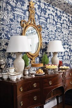 Antique sideboard (or buffet) with gorgeous wallpaper and gilded mirror. So elegant.