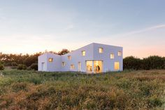 The defining concept for this house, commissioned by a photographer as both his summer house and studio, was based on developed facade studies which define a simple and smooth building skin varied in height and punctured by openings.  Two volumes define the main living & work spaces, both converge...