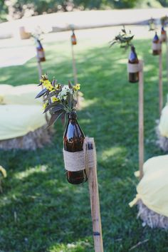 tall sticks with bottles attached for flowers to line the aisle