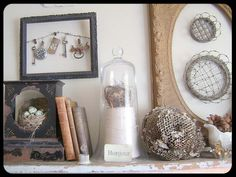Love the black frame with cool objects hanging off the black wire.  Vignette is interesting and has great texture.