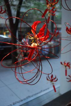 #vordemA Spherical shapes made of red wireaccented by hanging red and yellow Gloriosas. Pg 20