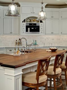 Absolutely love the mixture of Marble Countertops with a  wood countertop for the island with seating